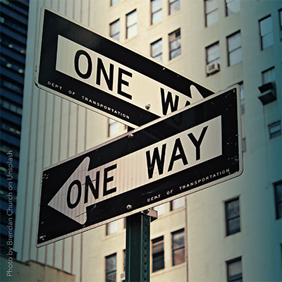 Road signs in different directions with the text: One way.