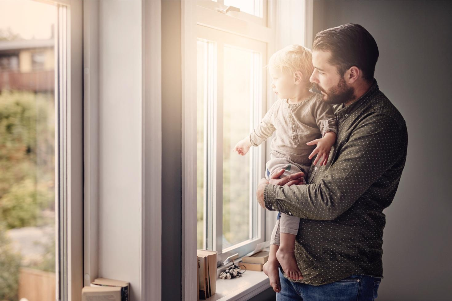 Father with child looking out of window
