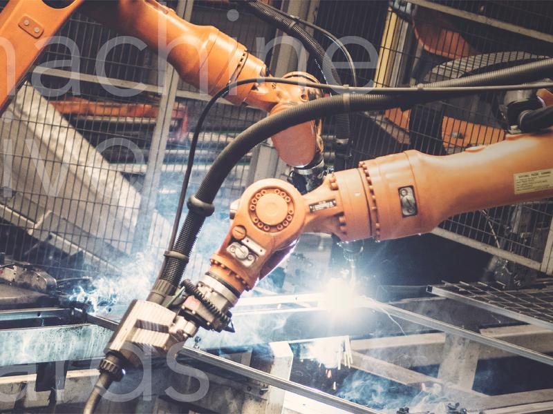 Industrial robots welding surrounded by mesh panels of Troax machine guarding.